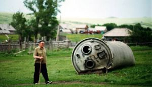 Hombre paseando junto a los restos de un cohete en un pueblecito del Altái. Foto: Jonas Bendiksen