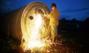 Chatarrero desguazando los restos de un cohete mientras anochece. Foto: Jonas Bendiksen